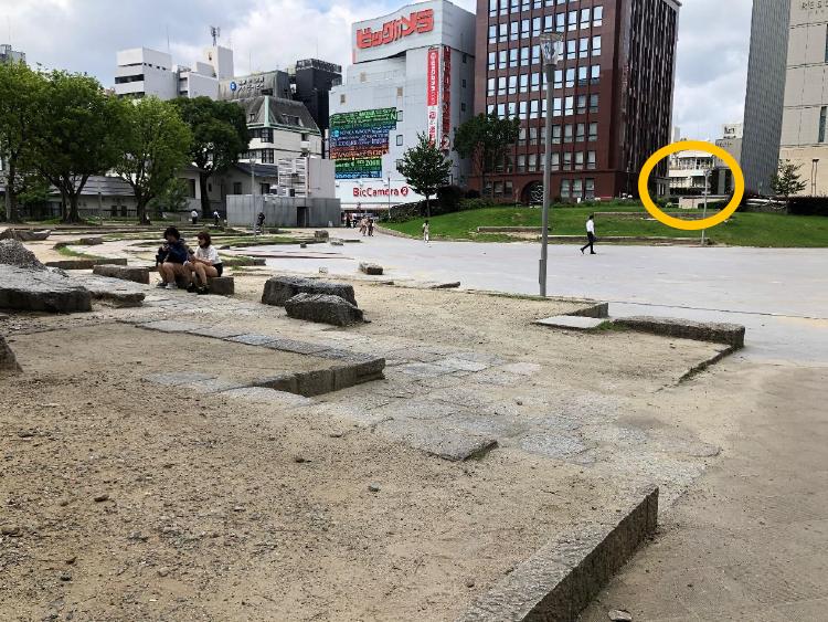 公園の広場を黄色の丸を目指して進んでください。